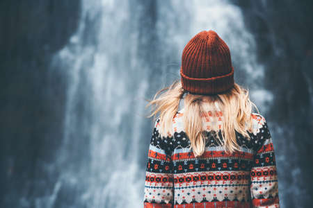 Woman and waterfall Travel Lifestyle adventure concept vacations into the wild wearing cozy sweater and hat Stock Photo
