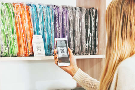 Woman shopping scanning qr code with smartphone on showcase sale advertising modern technology and fashion retail concept Stockfoto