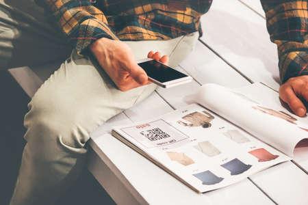 El hombre de compras escaneo de código QR con la publicidad de teléfonos inteligentes en el catálogo de ropa moderna tecnología y el concepto de distribución de moda