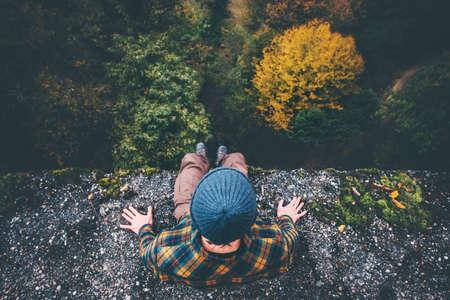 Homem Traveler sentada na borda penhasco ponte com a floresta vista aérea do curso férias estilo de vida de aventura conceito Banco de Imagens