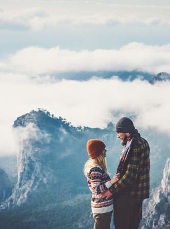 Couple lovers Man and Woman hugging with mountains and clouds landscape on background Love and Travel happy emotions Lifestyle concept. Young family traveling active adventure vacations Stock Photo