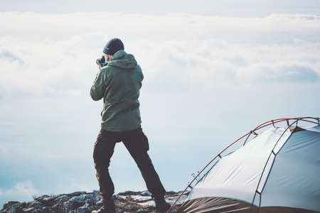 Man photographer with photo camera shooting foggy mountains clouds landscape from tent camping Travel Lifestyle concept adventure vacations outdoor Standard-Bild