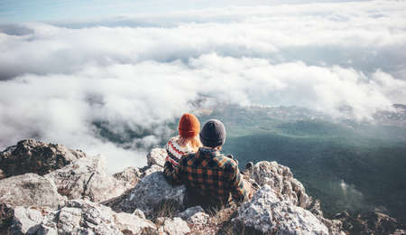 Couple Man and Woman sitting on cliff enjoying mountains and clouds landscape Love and Travel happy emotions Lifestyle concept. Young family traveling active adventure vacations Imagens