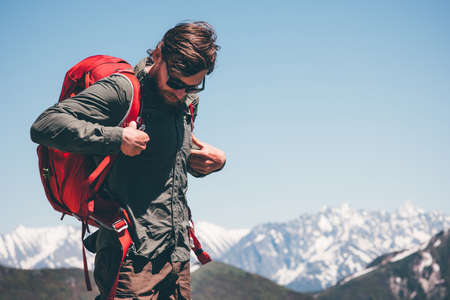 Man Traveler wearing backpack hiking in mountains Travel Lifestyle success concept adventure active vacations outdoor