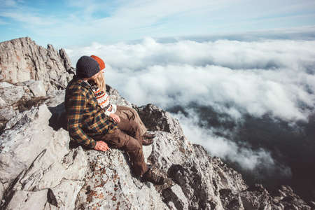 Couple travelers Man and Woman sitting on mountains cliff relaxing over clouds Love and Travel happy emotions Lifestyle concept. Young family traveling active adventure vacations
