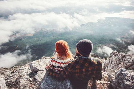 Couple homme et femme assise étreignant sur la falaise en appréciant les montagnes et les nuages ??paysage amour et Voyage émotions heureuses Lifestyle concept. Jeune famille voyageant des vacances d'aventure actifs Banque d'images