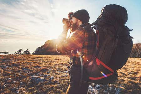 Man photographe avec grand sac à dos et appareil photo en prenant des montagnes coucher de soleil Voyage Lifestyle passe-temps Aventure vacances actives en plein air Banque d'images