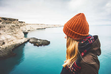 Young Woman enjoying cold sea view alone Travel Lifestyle concept adventure vacations outdoor. Blonde girl wearing fashion orange knitted hat and scarf. Melancholy solitude emotions