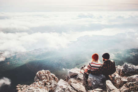 Couple travelers Man and Woman sitting on cliff relaxing mountains and clouds aerial view  Love and Travel happy emotions Lifestyle concept. Young family traveling active adventure vacations Stock Photo - 71302237