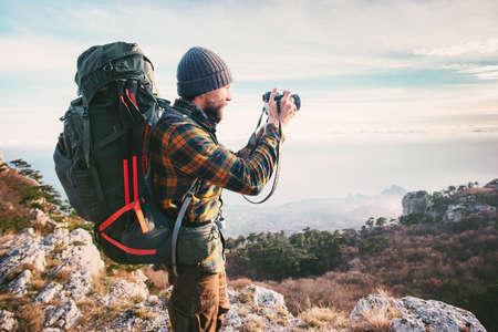 Man photographe avec sac à dos et appareil photo en prenant des montagnes Voyages Lifestyle vacances concept hobby aventure en plein air Banque d'images