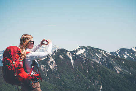 Femme heureuse montrant l'amour du c?ur par des mains de randonnée dans les montagnes avec des vacances actives à dos Voyage Lifestyle succès le concept d'aventure en plein air