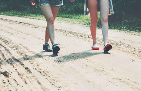 Voeten meisjes lopen op de weg Lifestyle Reizen en vriendschap begrip zomervakanties