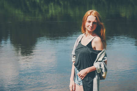 Pretty girl walking at river Lifestyle summer vacations harmony with nature concept. Young woman red hair wearing jeans shorts and top casual fashion clothing