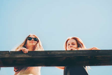 Couple girls friends walking together enjoy summer vacations blonde young women fashion lifestyle friendship happiness emotions concept blue sky on background Stockfoto