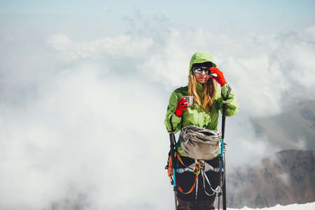 Woman climber drinking tea on mountain summit Travel Lifestyle adventure concept active vacations outdoor mountaineering sport clouds on background