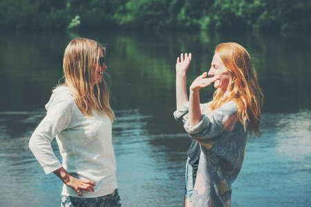s?urs Filles couple voyageant ensemble marchant au lac émotions heureuses de parler de la mode concept de mode de vie jeune femme appréciant amusant Banque d'images