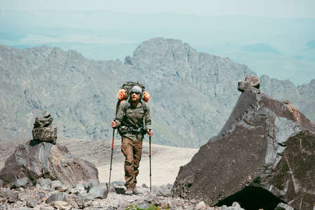 Traveler Man hiking in mountains with backpack Travel Lifestyle concept adventure active vacations outdoor mountaineering sport Stockfoto