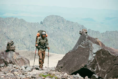 Traveler Man hiking in mountains Travel Lifestyle concept adventure active vacations outdoor mountaineering sport with backpack and trekking poles