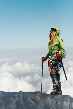 Happy Woman traveler climbing in mountains over clouds Travel Lifestyle adventure concept active vacations outdoor mountaineering sport success Stockfoto