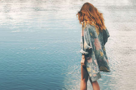 Young red hair woman walking at river alone wearing long cardigan Fashion Lifestyle concept and melancholy depression emotions Stock Photo