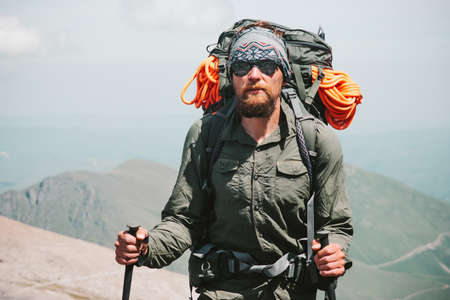 Bearded Man traveler hiking in mountains with backpack Travel Lifestyle concept adventure active vacations outdoor mountaineering sport Stockfoto