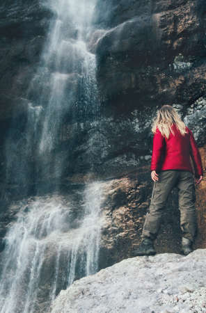 Woman Traveler enjoying waterfall view Travel Lifestyle adventure concept active vacations into the wild harmony with nature