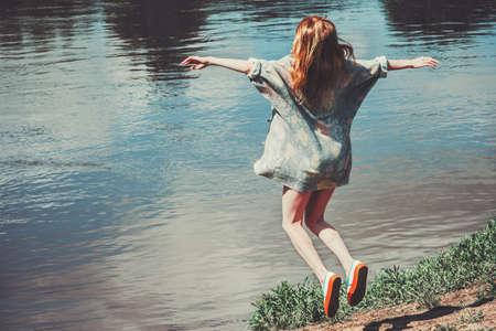 Gelukkige Vrouw springen vliegende levitatie rivierlandschap op de achtergrond Lifestyle Travel emoties succesconcept outdoor handen omhoog Stockfoto