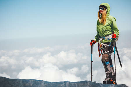 Woman traveler climbing in mountains over clouds Travel Lifestyle adventure concept active vacations outdoor mountaineering sport success