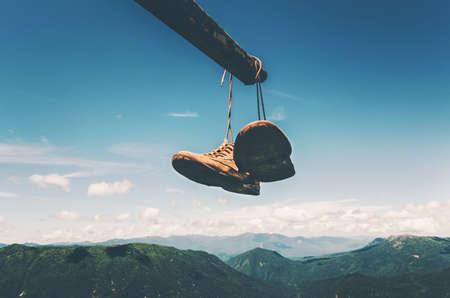 Chaussures de trekking bottes suspendue au-dessus des montagnes paysage aérien Voyage vacances d'aventure de style de vie concept de ciel bleu et les nuages ??sur fond