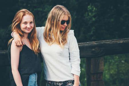 filles d'un couple marchant ensemble étreindre et heureux sourire appréciant les vacances d'été blond jeunes femmes mode de vie émotions notion Banque d'images