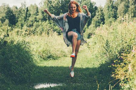 Jonge vrouw gelukkig springen zomervakanties bos landschap op de achtergrond Lifestyle Travel fun emoties succesconcept outdoor