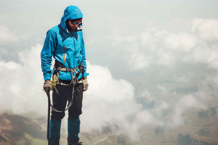Man climber on mountain summit Travel Lifestyle concept adventure active vacations outdoor mountaineering sport alpinism equipment Stockfoto