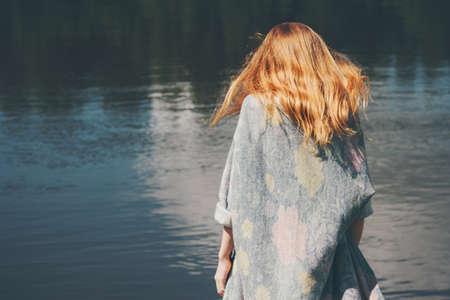 Jonge vrouw lopen op de rivier alleen het dragen van lange vest Fashion Lifestyle emoties concept rood haar op wind