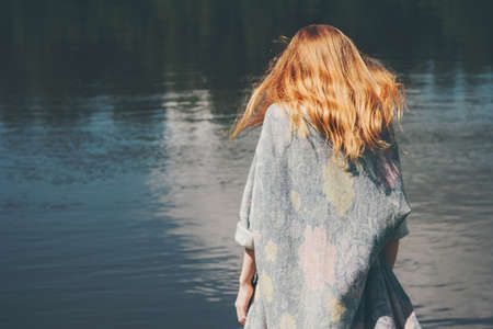 Young woman walking at river alone wearing long cardigan Fashion Lifestyle emotions concept red hair on wind