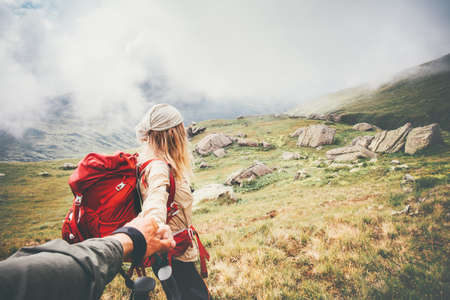 Couple travelers Man and Woman follow holding hands at foggy mountains landscape on background Love and Travel happy emotions Lifestyle concept. Young family traveling active adventure vacations Фото со стока