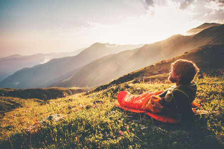 Man relaxing in sleeping bag enjoying sunset mountains landscape Travel Lifestyle camping concept adventure summer vacations outdoor hiking mountaineering harmony with nature Imagens