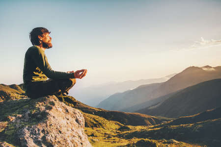 Man meditating yoga at mountains Travel Lifestyle relaxation emotional concept adventure summer vacations outdoor harmony with nature landscape