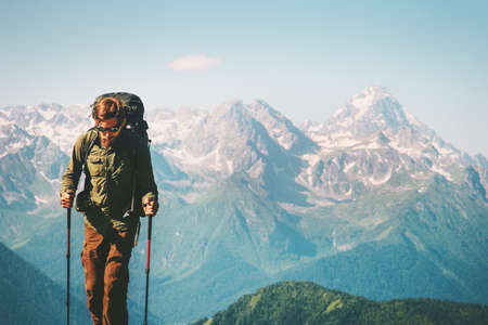Man Traveler at mountains hiking with backpack Travel Lifestyle concept adventure outdoor rocky mountains landscape on background