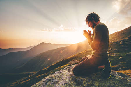 Man praying at sunset mountains Travel Lifestyle spiritual relaxation emotional concept vacations outdoor harmony with nature landscape Reklamní fotografie