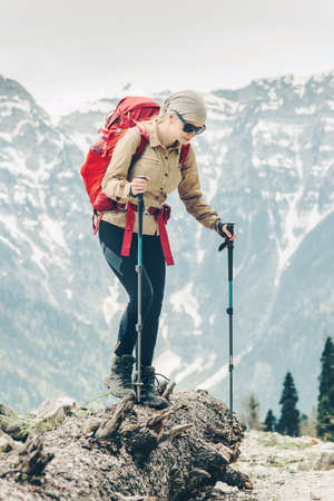 Young woman hiking with backpack at mountains Travel Lifestyle concept adventure summer vacations activity outdoor mountaineering alone into the wild