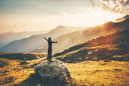 Man raised hands at sunset mountains Travel Lifestyle success and wellness emotional concept adventure vacations outdoor hiking harmony with nature aerial view Standard-Bild