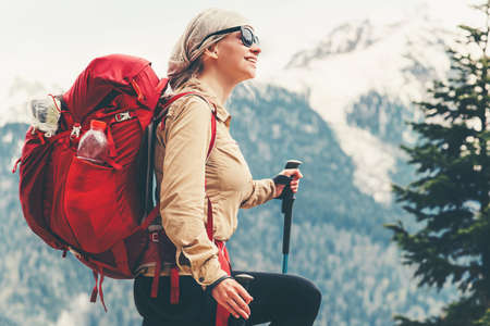 Happy woman traveling with red backpack hiking Travel Lifestyle concept adventure summer vacations outdoor mountains landscape on background Stock Photo