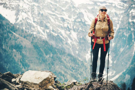 Woman traveling hiking with backpack at mountains Travel Lifestyle concept adventure summer vacations activity outdoor mountaineering alone into the wild Stock Photo