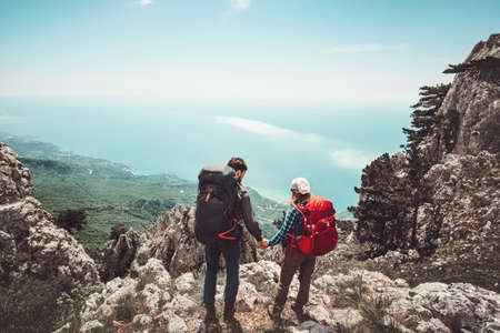 Couple travelers Man and Woman holding hands enjoying mountains aerial view Love and Travel Lifestyle concept. Young family traveling together active adventure vacations
