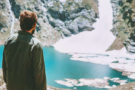 Man enjoying icy lake in mountains landscape Travel Lifestyle adventure concept summer vacations outdoor harmony with nature