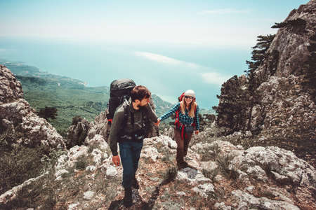 Couple Man and Woman holding hands hiking at mountains Love and Travel Lifestyle concept. Young family traveling together active adventure vacations