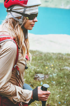 Woman hiking Travel Lifestyle wanderlust concept summer vacations outdoor. Girl with backpack and helmet blue lake on background