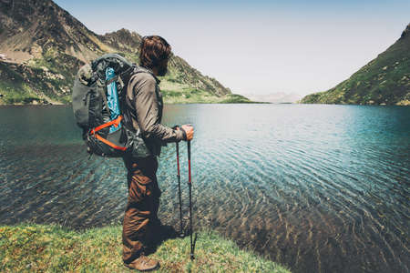 Man backpacker hiking at lake in mountains landscape Travel Lifestyle adventure concept summer vacations outdoor harmony with nature photo