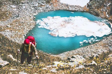 Hiker woman climbing at blue lake heart shaped mountains with backpack Travel Lifestyle adventure concept summer vacations outdoor active healthy life Stockfoto