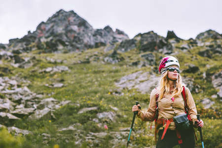 Woman climber hiking at rocky mountains Travel Lifestyle wanderlust concept summer vacations outdoor. Girl hiker with backpack and helmet climbing photo